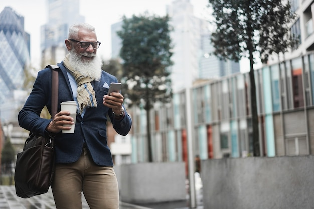Hombre de negocios senior inconformista que usa la aplicación de teléfono móvil mientras toma café mientras camina al trabajo - enfoque en la cara