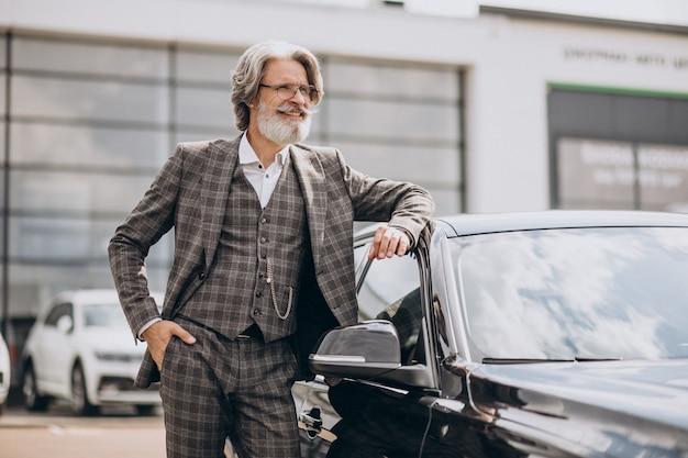 Hombre de negocios senior en una sala de exposición de coches eligiendo un coche