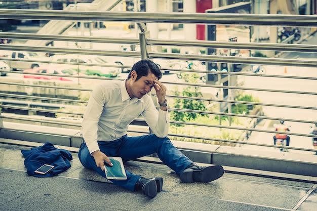 Hombre de negocios sentado afuera en el suelo después de ser despedido.