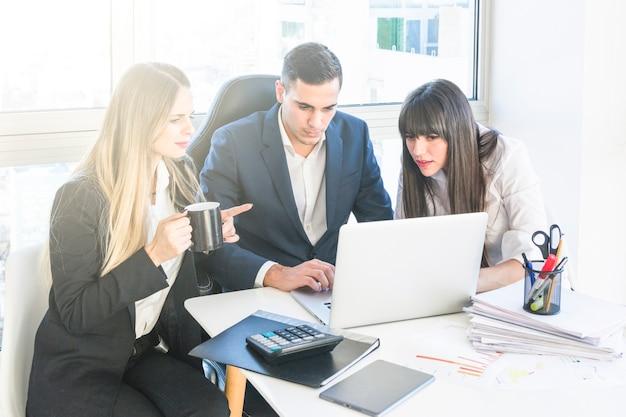 Hombre de negocios sentado con dos mujeres que trabajan en la oficina