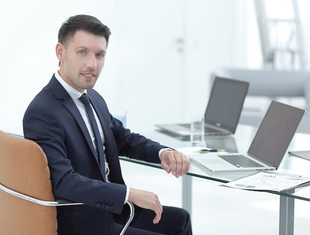 Hombre de negocios, sentado, en el escritorio