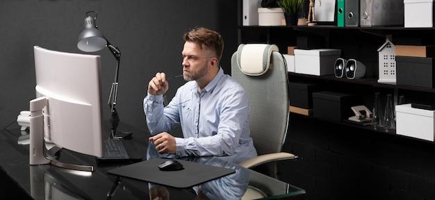 Hombre de negocios sentado en la oficina en el escritorio de la computadora y sosteniendo su boca grillete de gafas