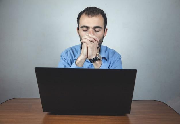 Hombre de negocios sentado en la oficina rezando.