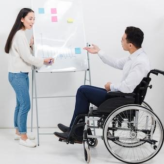 Un hombre de negocios sentado en silla de ruedas preguntando algo a una mujer joven dibujando un gráfico en la pizarra