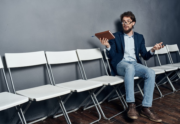 Hombre de negocios sentado en una silla con un trabajo portátil esperando una entrevista de trabajo. foto de alta calidad