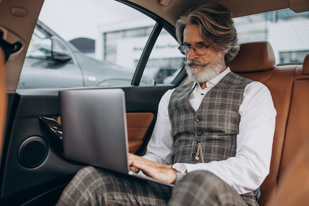 Hombre de negocios sentado en su coche en la parte trasera sentarse