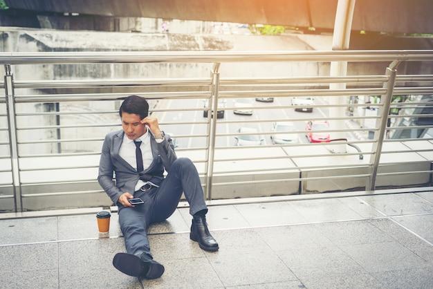 Hombre de negocios sentado en el suelo estresado.