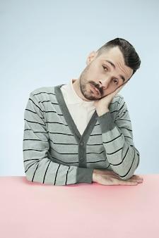 Hombre de negocios serio, aburrido y aburrido sentado en la mesa. el retrato en estilo minimalista