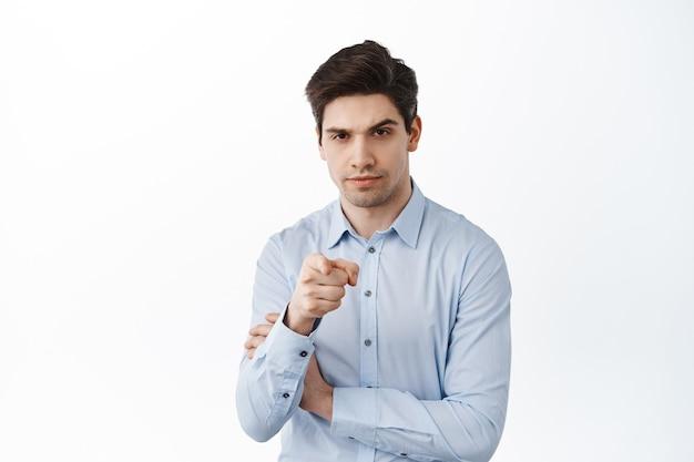 Hombre de negocios serio apuntando al frente, hablando contigo, eligiendo empleado, invitando a trabajar en su empresa, de pie sobre una pared blanca