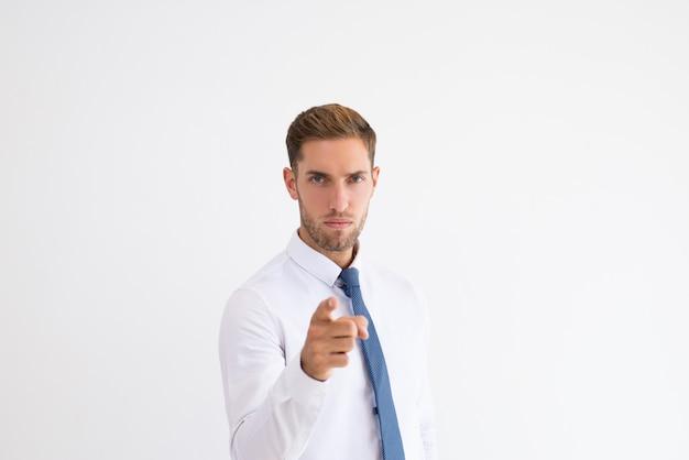 Hombre de negocios serio apuntando y mirando a la cámara