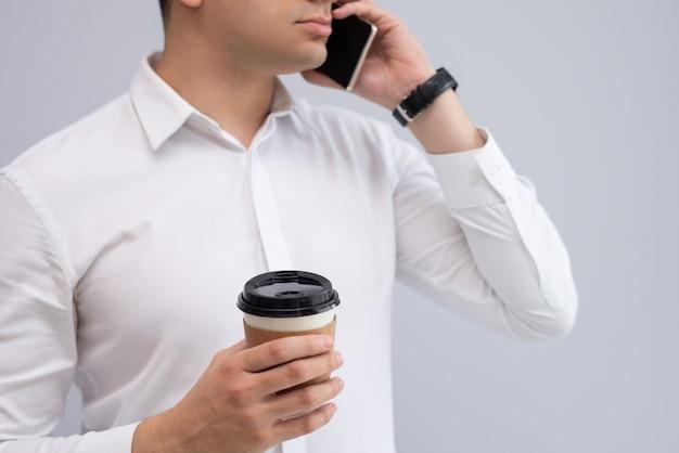Hombre de negocios serio con café para llevar que habla en el teléfono móvil