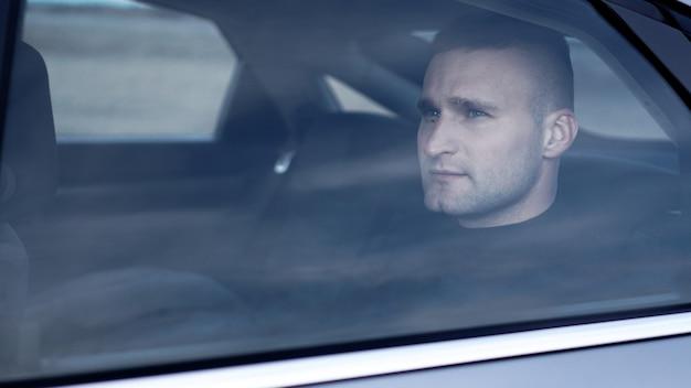 Hombre de negocios serio y centrado sentado en el asiento trasero del coche