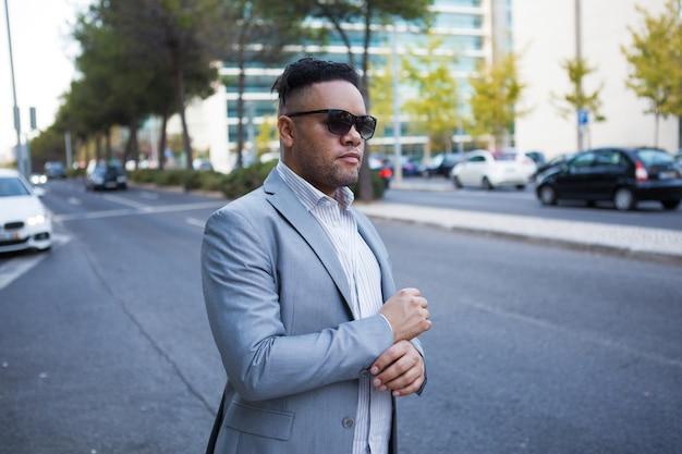 Hombre de negocios serio esperando taxi en la ciudad