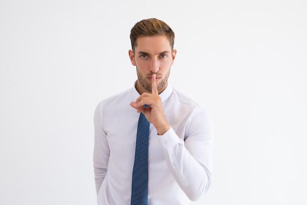 Hombre de negocios serio haciendo gesto de silencio