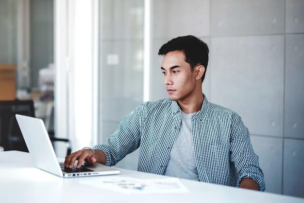 Hombre de negocios serio joven que trabaja en la computadora portátil de la computadora en oficina.