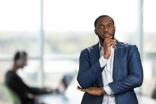 Hombre de negocios serio mantenga la barbilla en la mano. gerente joven guapo pensando en idea seria