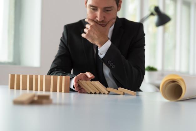 Hombre de negocios serio preocupado sentado en su escritorio deteniendo el efecto dominó con su mano mientras planea el futuro de su empresa.