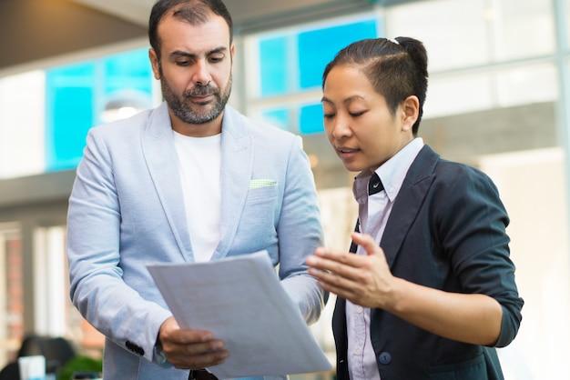 Hombre de negocios serio que discute el documento a la empresaria asiática