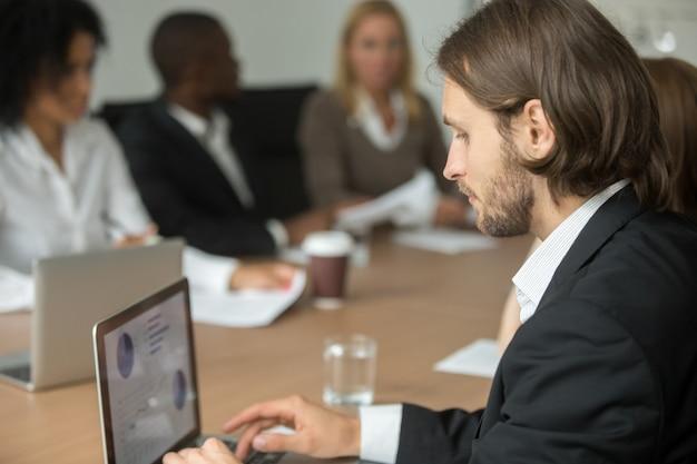 Hombre de negocios serio que trabaja en la computadora portátil en línea en la reunión diversa del grupo
