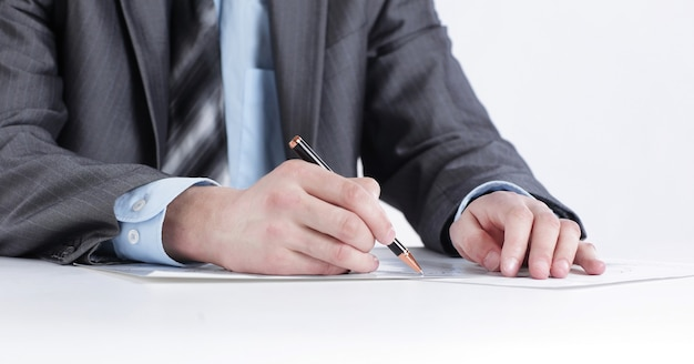 Hombre de negocios serio que trabaja con documentos sentado en un escritorio aislado sobre fondo blanco.