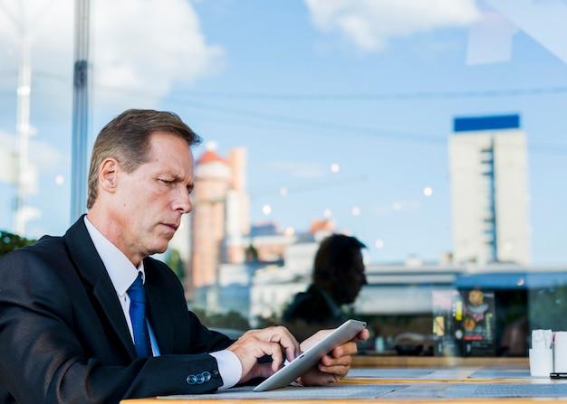 Hombre de negocios serio que usa la tableta digital en restaurante