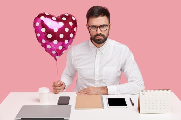 Hombre de negocios serio recibe san valentín de su novia en el lugar de trabajo, sostiene un globo en forma de corazón, posa en el escritorio