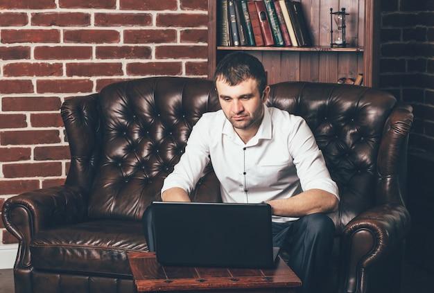 El hombre de negocios se sienta en un sofá de cuero detrás de una computadora portátil en el interior de la habitación. un hombre trabaja en gabinete propio.