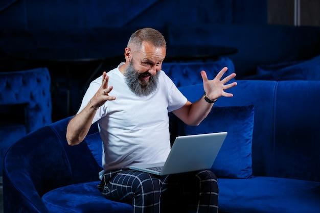 Hombre de negocios se sienta con una taza de café y hace un nuevo proyecto con muecas en su rostro.
