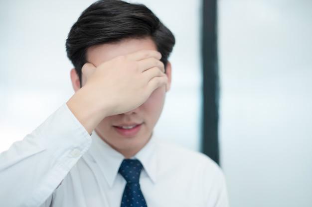 El hombre de negocios siente la cabeza en su corazón mientras trabaja en la oficina, concepto médico
