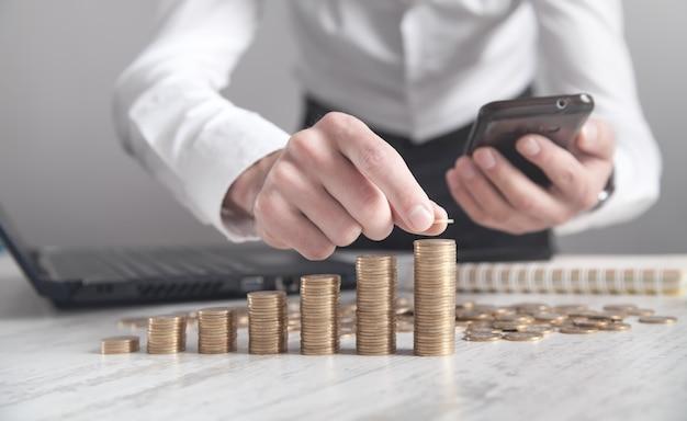 Hombre de negocios con smartphone y apilar monedas en el escritorio.