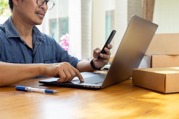Hombre de negocios de sme que trabaja en la computadora portátil mientras mira el teléfono celular con la caja del paquete en la tabla