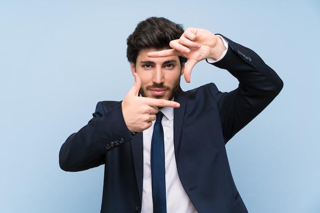 Hombre de negocios sobre cara de concentración aislada de la pared azul. símbolo de encuadre
