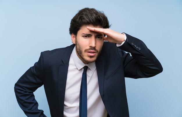 Hombre de negocios sobre la pared azul aislada que mira lejos con la mano para mirar algo