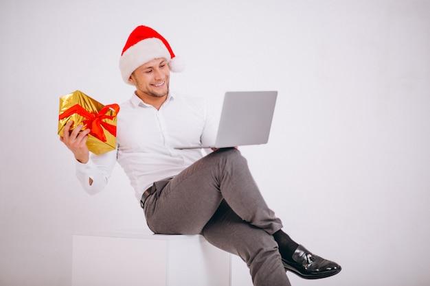 Hombre de negocios en el sombrero de santa que hace compras en línea en la navidad