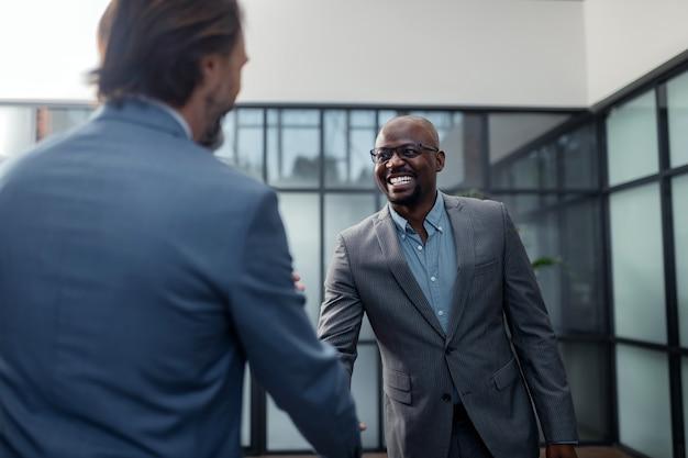 Hombre de negocios sonriendo. alegre empresario de piel oscura sonriendo mientras habla con su colega
