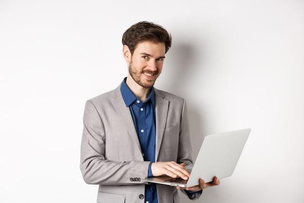 Hombre de negocios sonriente acertado que trabaja en la computadora portátil y que mira feliz a la cámara, de pie en traje gris sobre fondo blanco.