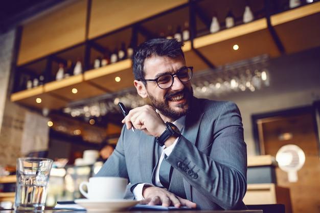 Hombre de negocios sonriente caucásico elegante atractivo en traje y con los anteojos sentado en la cafetería y escribiendo en la agenda. en primer plano está el café en un vaso de agua.