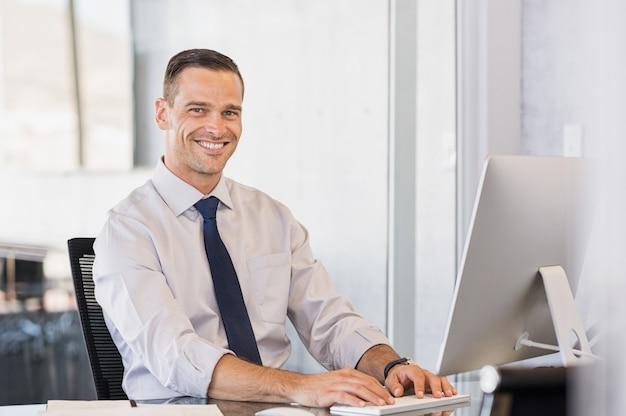 Hombre de negocios, sonriente, en computadora
