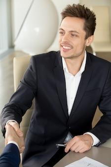 Hombre de negocios sonriente joven que sacude la mano masculina en la reunión, primer im