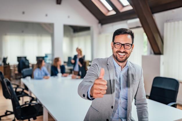 Hombre de negocios sonriente que da los pulgares para arriba delante de su equipo.