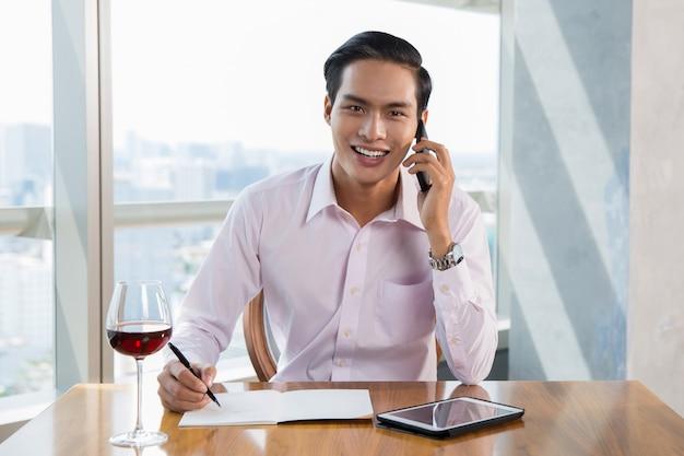 Hombre de negocios sonriente que habla en el teléfono inteligente de asia