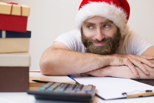Hombre de negocios sonriente que lleva el sombrero de papá noel y que se relaja