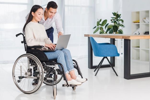 Hombre de negocios sonriente que muestra algo a su mujer joven discapacitada en el ordenador portátil en la oficina