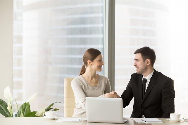 Hombre de negocios sonriente que sacude las manos con la empresaria