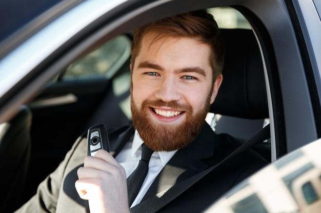 Hombre de negocios sonriente que se sienta en un coche que muestra nuevas llaves del coche
