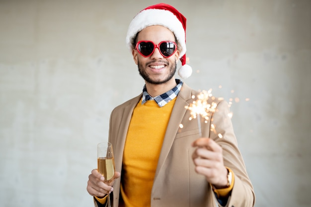 Hombre de negocios sonriente en ropa casual elegante, gorro de papá noel y gafas de sol en forma de corazón con flauta de champán y luz de bengala brillante