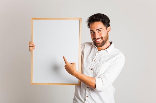 Hombre de negocios sonriente señalando la pizarra blanca