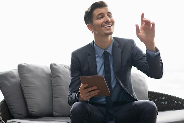 El hombre de negocios sonriente con la tableta de llamada del camarero
