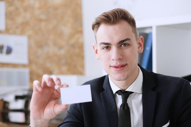 Hombre de negocios sonriente en traje sostenga la tarjeta de visita
