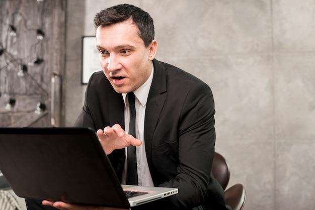 Hombre de negocios sorprendido joven que hojea el ordenador portátil en casa
